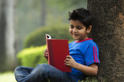 child-reading-under-tree