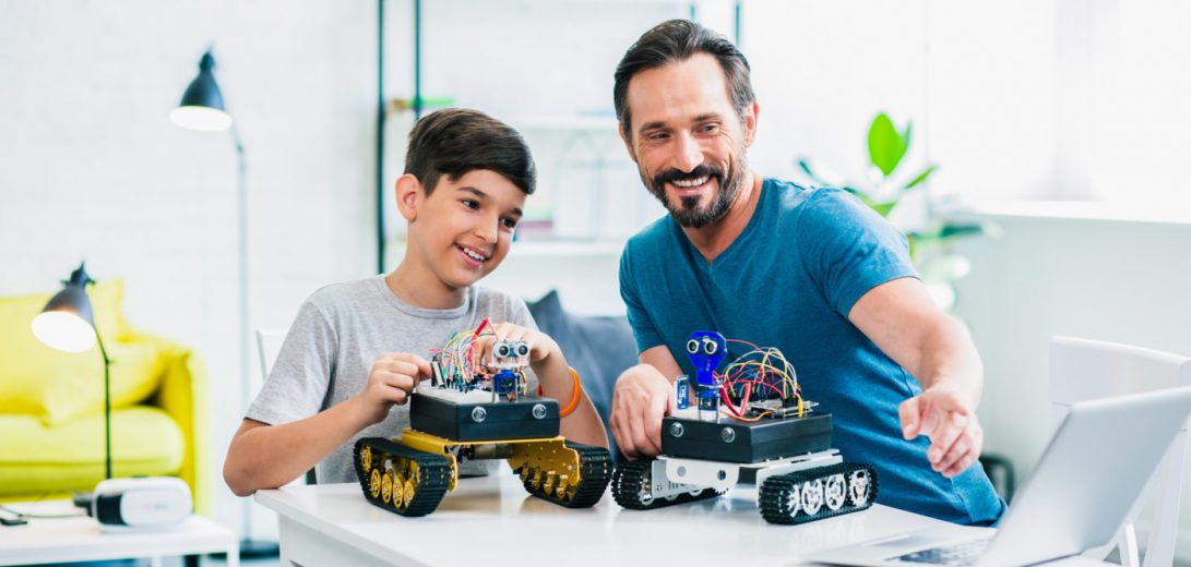 Optimistic father and son enjoying their robotic hobby